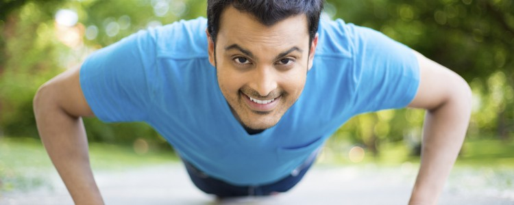 Closeup portrait, young healthy handsome man performing pushup outside on road in park, isolated trees and sky background.