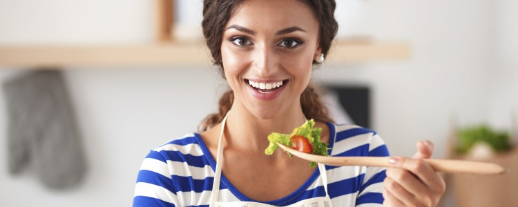 Young woman eating fresh salad in modern kitchen, isolated